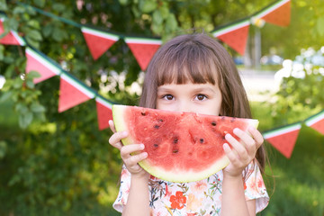 Little girl. Juicy red watermelon slice. Summer sunny day. Bright Grass