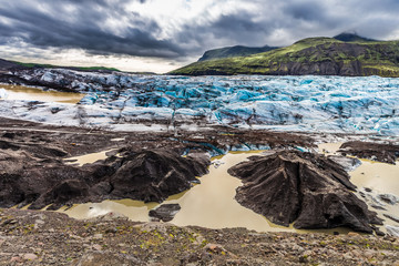 Blue and black glacier and green mountains, Iceland