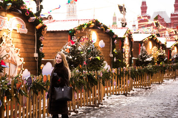 Portrait in full growth, Russian beautiful woman in a mink coat on the Red Square in Moscow in Christmas time