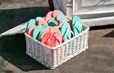 many sandal have many color. Schists pink and green in a basket
