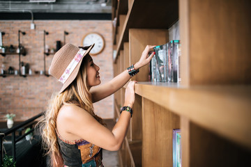 young girl takes a book from the shelf, in the library