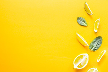Pieces of lemon, lime and green mint leaves on a yellow background. Summer products for making lemonade. Top view, flat lay, copyspace