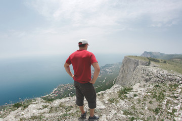 man hiker stands on the edge of cliff