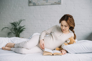 attractive pregnant woman lying on bed with teddy and reading book in bedroom