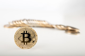 Gold Bitcoin on bitcoins background on gray surface..