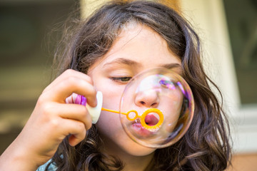 Close up of young caucasian girl child blowing soap bubbles.