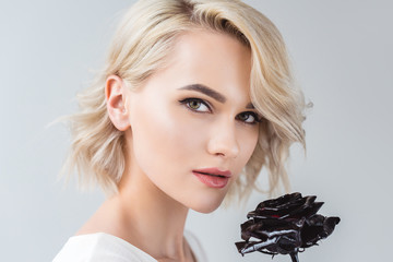 portrait of attractive blonde girl with black rose, isolated on grey