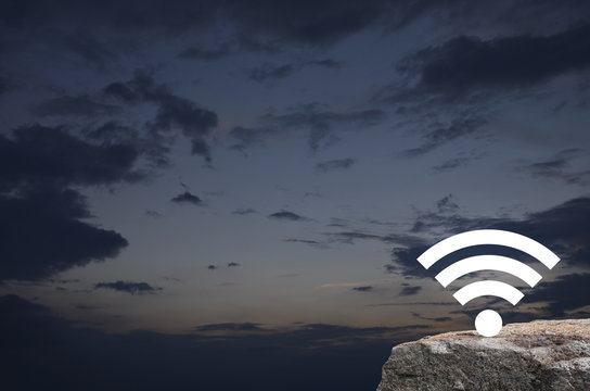 Wi-fi button on rock mountain over sunset sky, Technology and internet concept