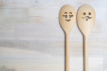 Wooden spoon with funny faces, woman and man, on wooden background