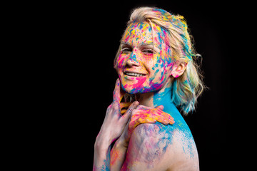 attractive cheerful girl posing in colorful holi paint, isolated on black