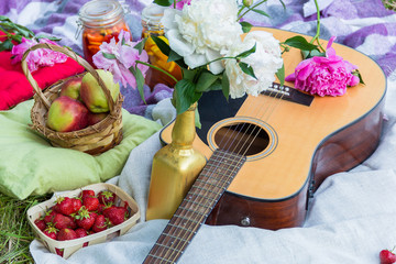 Picnic in the outdoor with guitar, apples, strawberry, beverages, pillows and peonies