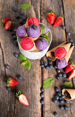 Ice cream, Blueberry and Raspberry scoop in cone on wooden table.