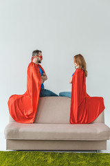 super couple in masks and cloaks sitting on couch and looking at each other on grey