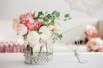 Decoration for wedding party in romantic vintage style.  Decorative cell with gentle pink flowers on a white table