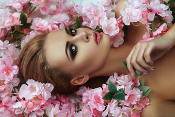 Beautiful blondie model is emotionally posing with flowers