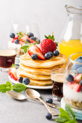 Breakfast composition with fresh pancakes and berries on light gray concrete background. Healthy food concept with copy space.