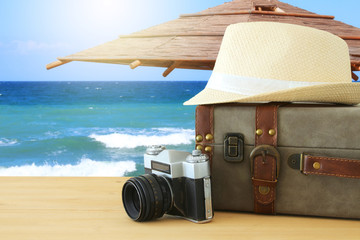 traveler vintage luggage, camera and fedora hat over wooden table infront of sea landscape. holiday and vacation concept.