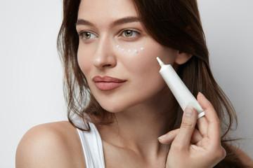 Eye Skin Care. Beautiful Woman Applying Eye Cream