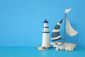 nautical concept with white decorative sail boat, lighthouse, seashells over blue wooden table and background.