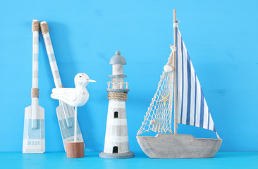 nautical concept with white decorative seagull bird, lighthous, wooden oars and boat oars over blue background.