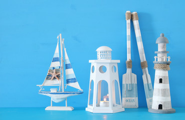 nautical concept with white decorative lantern, lighthous, wooden oars and boat oars over blue background.