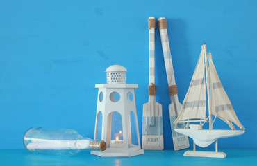 nautical concept with white decorative lighthouse lantern, wooden oars, letter in the boat and boat over blue background.
