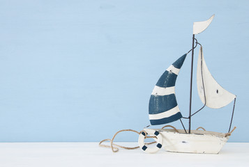 nautical concept with sail boat over white wooden table