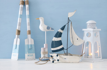 nautical concept with white decorative seagull bird, lighthous lantern, wooden oars and boat over blue background.