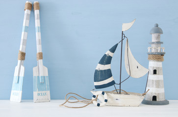 nautical concept image with decorative oars, boat and lighthouse over light blue background.