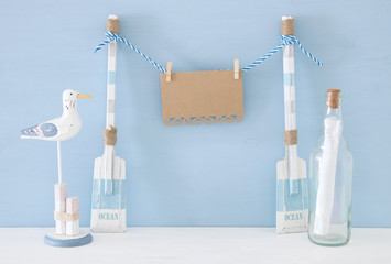 nautical concept with hanging empty note on a string next to letter in the bottle and seagull over blue background.