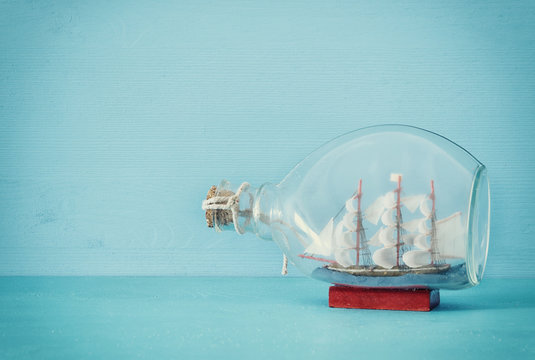 nautical concept image with sail boat in the bottle over blue wooden table and background. Selective focus.
