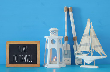 nautical concept with white decorative lighthouse lantern, wooden oars and boat next to blackboard over blue background.