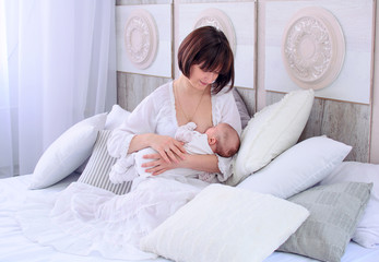 Breastfeeding baby. Young mother holding her newborn child. Mom nursing baby. Woman and new born relax in a white bedroom. Mother breast feeding baby.