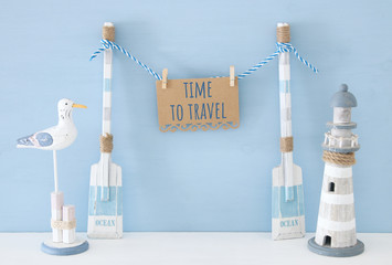 nautical concept with wooden decorative boat oars and hanging note message on a string next to lighthouse and seagull over blue background.