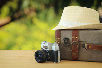 traveler vintage luggage, camera and fedora hat over wooden table infront of bokeh landscape. holiday and vacation concept.