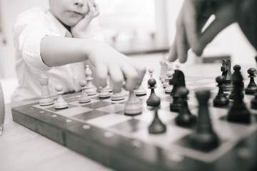 Child playing chess, shallow depth of field and monochrome