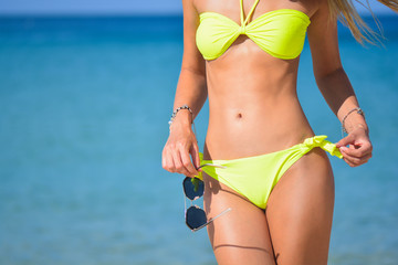 beautiful fit young woman in sexy yellow bikini at the beach. Girl with sunglasses, summer time near blue sea. Girl's abs
