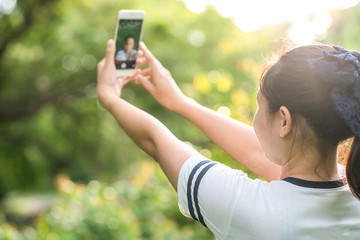 woman taking photo with smart phone at park with sunshine
