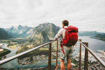 Adventurer man with red backpack enjoying mountains scenery Travel Lifestyle adventure vacations traveler standing alone on Rampestreken viewpoint in Norway Wall mural