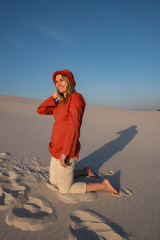 Joyful young woman, blonde in red hat relaxes in the desert