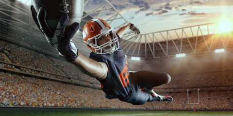 American football player jumps and catches the ball in flight in professional sport stadium Wall mural