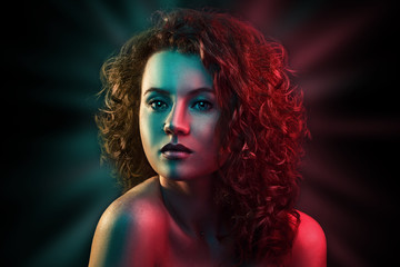Portrait of cute red head girl with curly hair in colorful bright lights posing in studio