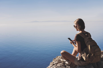 Young traveler woman on a hiking trail using smartphone, travel and active lifestyle concept