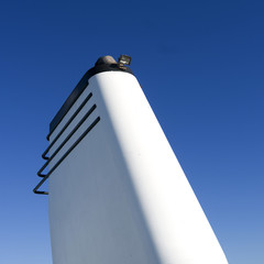 Seafaring: White funnel of RoRo vessel in front of a bright blue sky