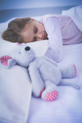 Child little girl sleeps in the bed with a toy teddy bear.
