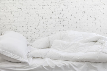 White bedding sheets and pillow in white room background. Messy bed concept in moring time.