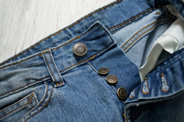 Blue jeans, close up. Wooden background. Fashionable concept