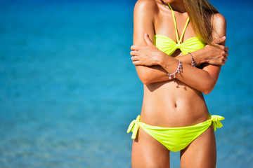 beautiful fit young woman in sexy yellow bikini at the beach. Summer time near blue sea. Girl's abs