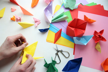 Man doing origami. Multicolored Origami and paper on  a white table.
