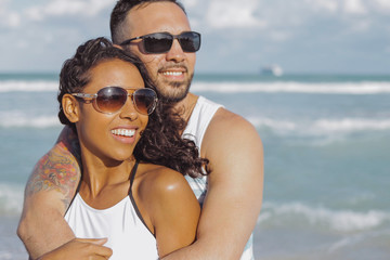 Happy handsome man embracing beautiful African-American girlfriend standing on background of ocean and looking away.